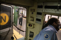 Desmond Hill, a vaccinated MTA conductor, looks out his crew cab window to check the platform for late-arriving passengers as he works the N subway line from Brooklyn's Coney Island to Queen's Astoria-Ditmars neighborhoods, Friday, Aug. 13, 2021, in New York. As New York City recovers from the COVID-19 pandemics' peak ridership on the aging transit system continues to rebound as authorities encourage mask and social distancing protocols to stem further transmission of the virus. (AP Photo/John Minchillo)