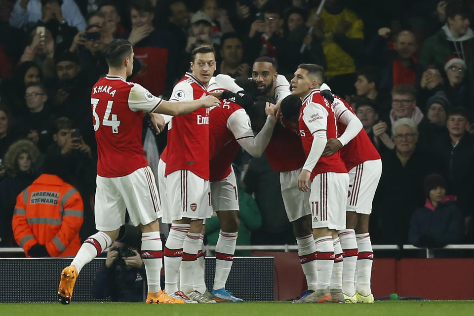 Arsenal's French-born Ivorian midfielder Nicolas Pepe celebrates with teammates after scoring the opening goal of the English Premier League football match between Arsenal and Manchester United at the Emirates Stadium in London on January 1, 2020. (Photo by Ian KINGTON / IKIMAGES / AFP) / RESTRICTED TO EDITORIAL USE. No use with unauthorized audio, video, data, fixture lists, club/league logos or 'live' services. Online in-match use limited to 45 images, no video emulation. No use in betting, games or single club/league/player publications. (Photo by IAN KINGTON/IKIMAGES/AFP via Getty Images)