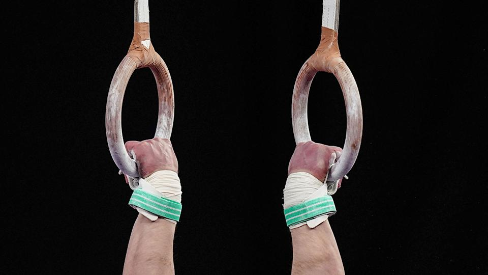 Pictured here, an Australian gymnasts holds on to rings during competition.
