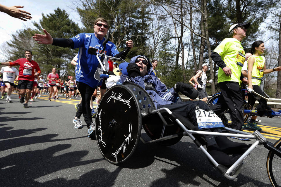 FILE - In this April 15, 2013, file photo Dick Hoyt, left, pushes his son Rick along the Boston Marathon course in Wellesley, Mass. Dick Hoyt, who last competed with his son in the Boston Marathon in 2014, has died, the Boston Athletic Association announced Wednesday, March 17, 2021. He was 80. (AP Photo/Michael Dwyer, File)