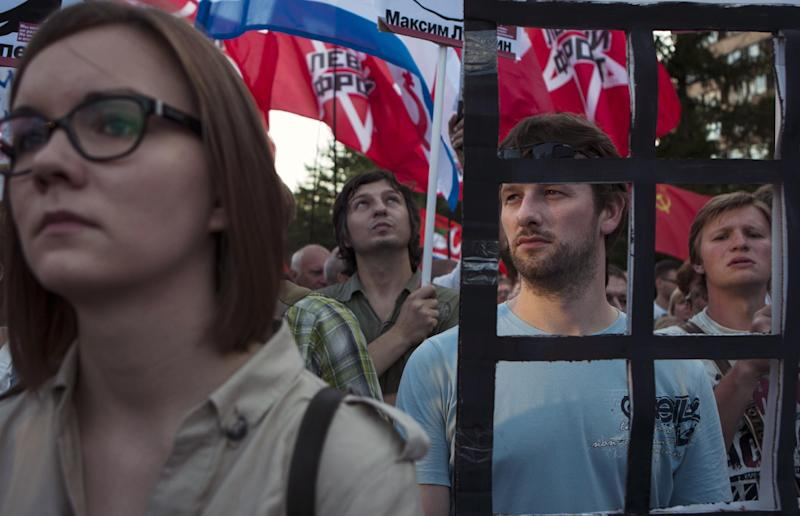 Demonstrators stand behind symbolic bars during an opposition rally in support of opposition activists they allege were arrested over their role in a violent protest in May, in Moscow, Thursday, July 26, 2012. Opposition activists and rights groups called the arrests a part of a widening government crackdown on dissent that followed Vladimir Putin's election to a third presidential term in March. (AP Photo/Alexander Zemlianichenko)