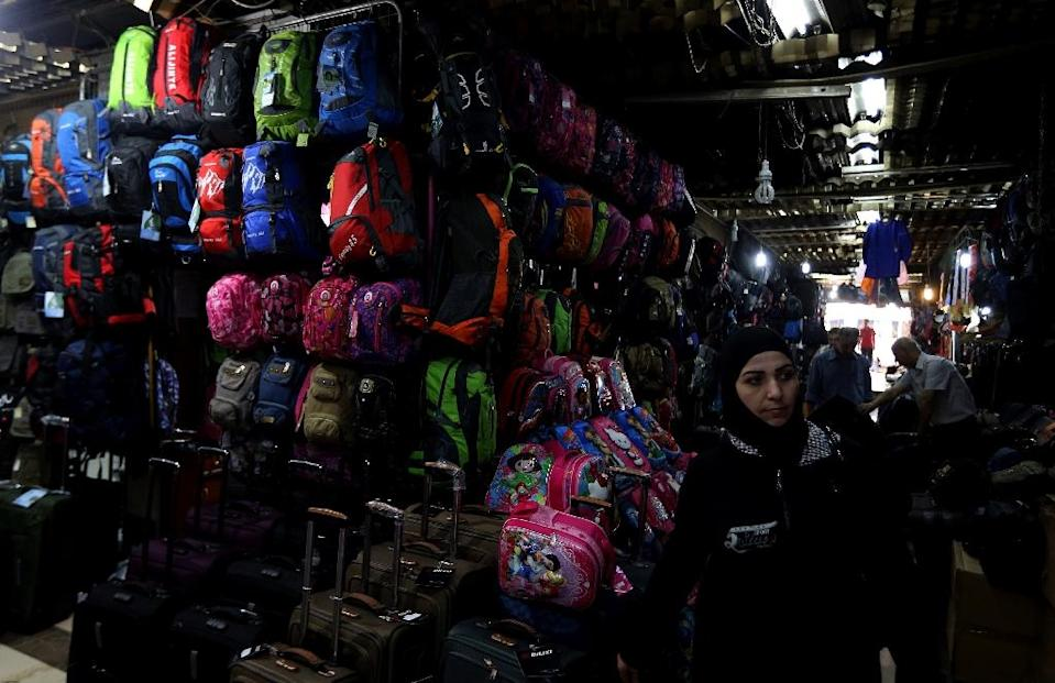 A Syrian woman looks at backpacks and suitcases for sale at a market in Damascus on September 22, 2015 (AFP Photo/Louai Beshara)