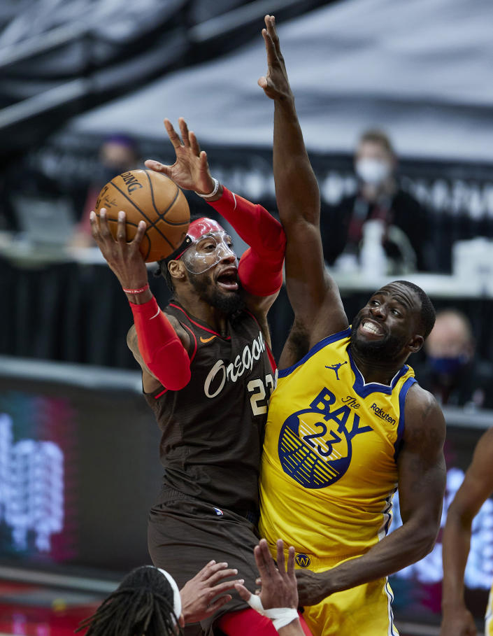 Portland Trail Blazers forward Robert Covington, left, shoots over Golden State Warriors forward Draymond Green during the second half of an NBA basketball game in Portland, Ore., Wednesday, March 3, 2021. (AP Photo/Craig Mitchelldyer)