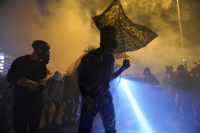 Protestors stand amid smoke on a bridge over a highway leading to the Cross Harbour Tunnel in Hong Kong, Nov. 17, 2019. (Photo: Vincent Yu/AP)