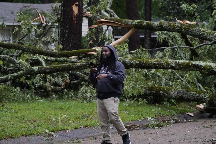 A northeast Jackson, Miss., resident talks with a friend on a phone as he inspects the wind toppled trees in his neighborhood, Tuesday, May 4, 2021. The severe weather was not unexpected, since the state was hit with a number of tornadoes on Sunday. (AP Photo/Rogelio V. Solis)