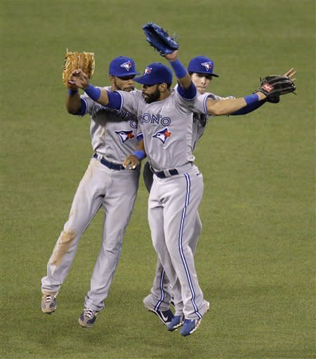 Toronto Blue Jays left fielder Eric Thames, left, right fielder Jose Bautista, center, and center fielder Colby Rasmus, right celebrate their 9-5 win against the Kansas City Royals after a baseball game on Saturday, April 21, 2012, in Kansas City, Mo. (AP Photo/Charlie Riedel)