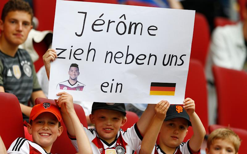 "A boy holds a poster ""Jerome move in as our neighbour""  - Credit: AP"