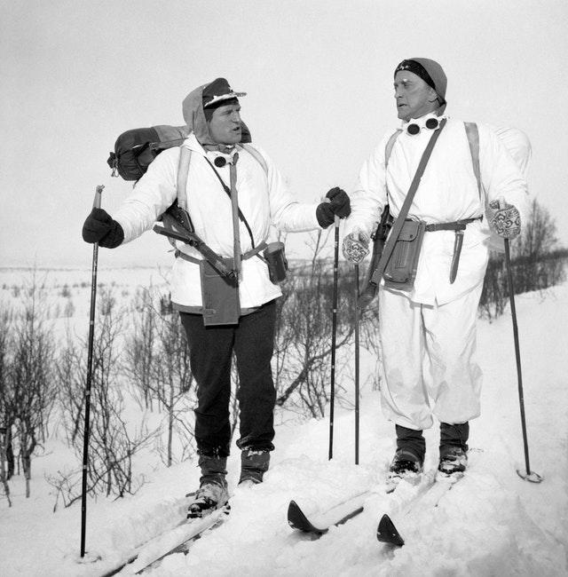 Richard Harris (left) and Kirk Douglas plough through heavy snow for the war film The Heroes of Telemark (PA)