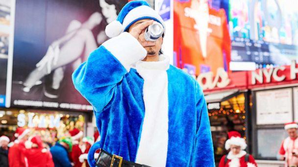 PHOTO: A person dressed as Santa Claus drinks a beer at Father Duffy Square for SantaCon on Dec. 14, 2019 in New York City. Every year, people dress up as Santa Claus or in other holiday-themed costumes and drink at multiple bars across the city. (Gabby Jones/Getty Images)