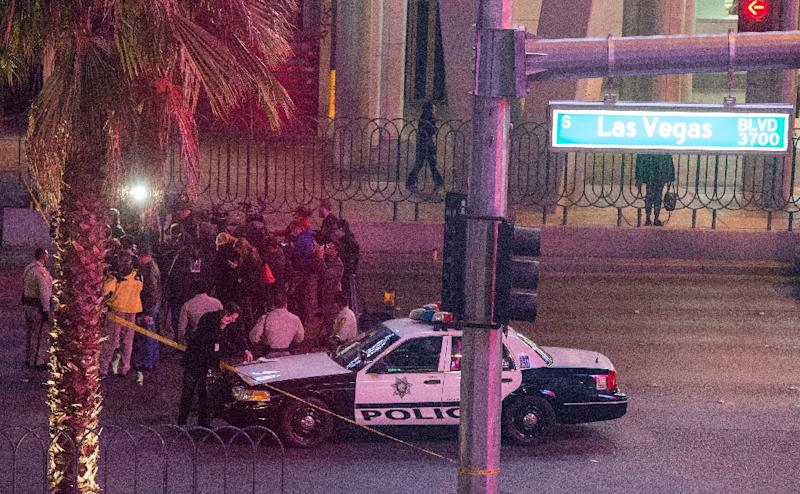 Police and members of the media are pictured along part of the Las Vegas Strip after a car ran into a group of pedestrians, on December 20, 2015 (AFP Photo/Valerie Macon)