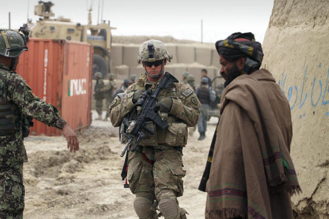 """A U.S. soldier, part of the NATO-led International Security Assistance Force (ISAF), stands outside a military base in Panjwai, Kandahar province south of Kabul, Afghanistan, Sunday, March. 11, 2012. Afghan President Hamid Karzai says a U.S. service member has killed more than a dozen people in a shooting including nine children and three women. Karzai called the attack Sunday """"an assassination"""" and demanded an explanation from the United States. He says several people were also wounded in the attack on two villages near a U.S. base in the southern province of Kandahar. (AP Photo/Allauddin Khan)"""