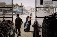 <p>A woman begs outside a grocery store in Azzan, a pivotal southern crossroads town that had seesawed back and forth between government and insurgent forces in Yemen, on 22 May 2018. (Lorenzo Tugnoli/ The Wa) </p>