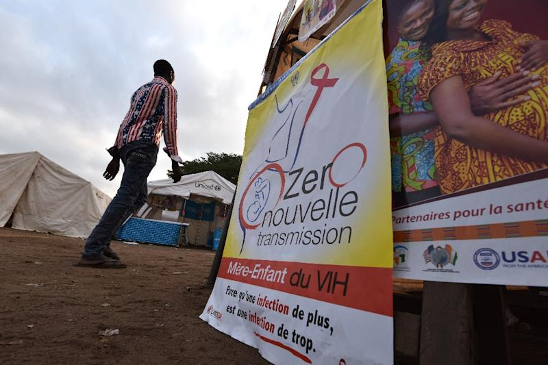 "A man walks past a poster reading, ""Zero new transmission from mother to child"", on December 1, 2014, in Abidjan (AFP Photo/Sia Kambou)"