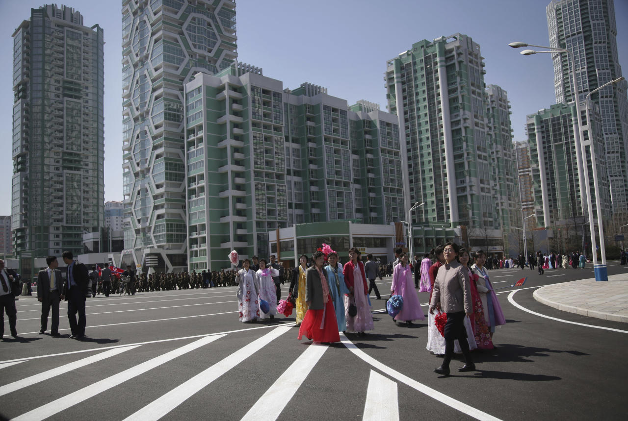 FILE - In this April 13, 2017, file photo, North Korean men, women and soldiers walk past apartment blocks along Ryomyong street, a collection of more than a dozen apartment buildings in Pyongyang, North Korea. North Korea under leader Kim Jong Un has been on a spending spree, evidenced in projects like the new Ryomyong Street residential district. But outside economists looking for clues of the country's fiscal health say its latest budget reveals conflicting desires to keep up appearances, especially for potential foreign investors, while obscuring even the most basic economic indicators. (AP Photo/Wong Maye-E, File)
