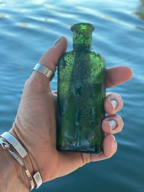 Jennifer Dowker finds green bottle on top of a fish bed when she was cleaning the windows on the bottom of her boat, the Yankee Sunshine.