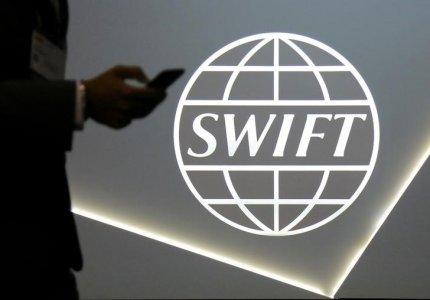 FILE PHOTO: A man using a mobile phone passes the logo of global secure financial messaging services cooperative SWIFT at the SIBOS banking and financial conference in Toronto, Ontario, Canada October 19, 2017. REUTERS/Chris Helgren /File Photo