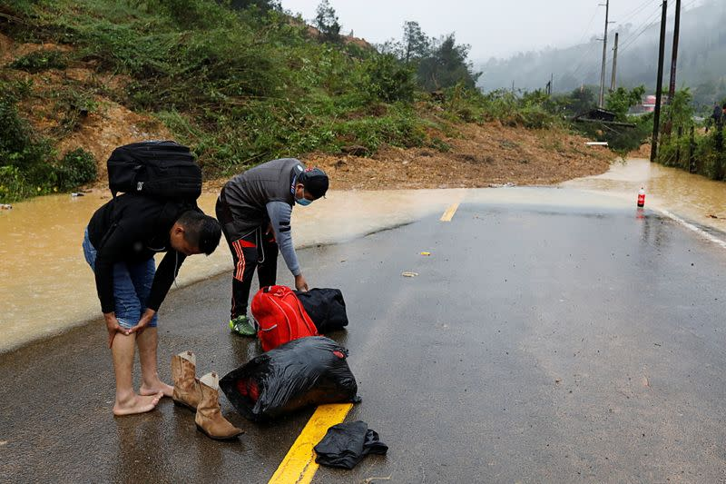 Men prepare to cross a mudslide blocking a road after the passage of Storm Eta, in Purulha