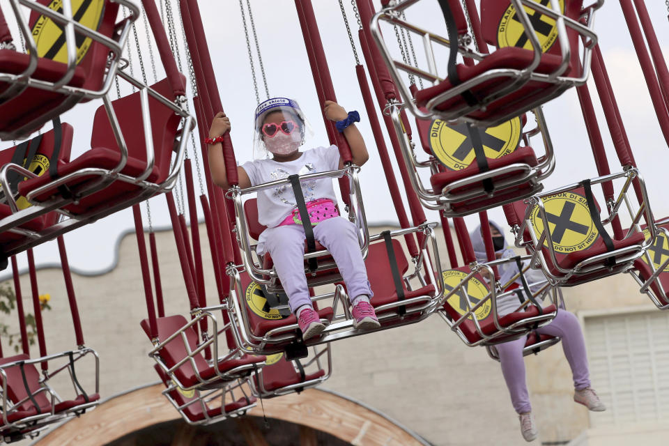 A young girl wearing a protective face shield enjoys a swing ride as physical distancing markings are seen on the seats during the first day of the reopening of Dunia Fantasi Amusement Park after weeks of closure due to the large-scale restrictions imposed to help curb the new coronavirus outbreak, at Ancol Dream Park in Jakarta, Indonesia, Saturday, June 20, 2020. (AP Photo/Tatan Syuflana)