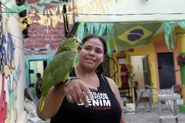 Claudiane Vidal holds a parrot outside of her home decorated in the colors of the Brazilian flag during the 2014 soccer World Cup in Fortaleza, Brazil, Monday, June 16, 2014. (AP Photo/Marcio Jose Sanchez)