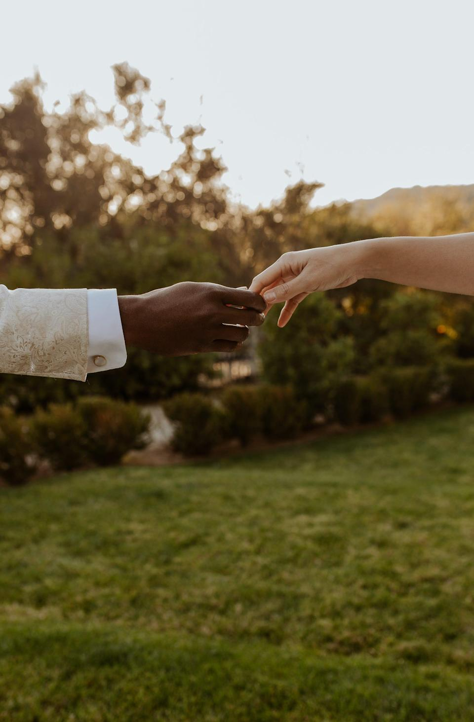 A black hand and a white hand reach towards each other in front of a field.