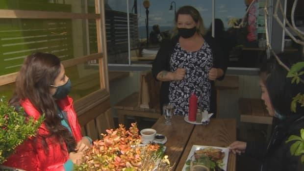 Jennie Silk serves food to two patio diners at Uli's Restaurant in White Rock on Saturday. (Doug Kerr/CBC NEws - image credit)