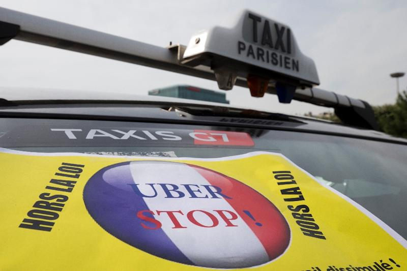 A taxi blocks an area in Paris as taxi drivers protest against what they see as unfair competition from Uber, which puts customers in touch with private drivers at prices lower than those of traditional taxis (AFP Photo/Kenzo Tribouillard)