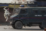 A masked Kashmiri protester jumps on the bonnet of an armored vehicle of Indian police as he throws stones at it during a protest in Srinagar, Indian controlled Kashmir, May 31, 2019. The image was part of a series of photographs by Associated Press photographers which won the 2020 Pulitzer Prize for Feature Photography. (AP Photo/Dar Yasin)