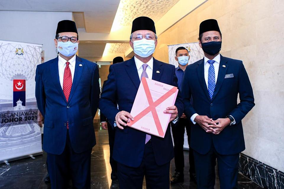 Johor Mentri Besar Datuk Hasni Mohammad (centre) holding up a copy of Johor Budget 2021 at the state assembly in Kota Iskandar. — Picture courtesy of the Johor Mentri Besar's office