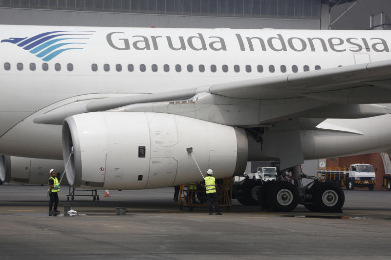 FILE - In this Sept. 28, 2015, file photo, workers clean a Garuda Indonesia jetliner at Garuda Maintenance Facility in Tangerang, Indonesia. Indonesia's state-owned enterprise minister said Thursday, Dec. 5, 2019, he will fire and seek the prosecution of the head of the national airline after he was implicated in the smuggling a Harley Davidson motorcycle into the country on a new jet. (AP Photo/Dita Alangkara, File)