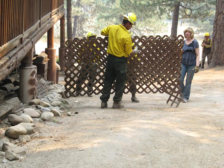 Denise Freeman, right, helps firefighters remove the wooden lattice on the side of her log home in Featherville, Idaho on Wednesday, Aug. 15, 2012. Freeman was among residents warned that they will likely have to evacuate their homes because of a nearby wildfire burning on 100 square miles, less than five miles from Featherville. (AP Photo/Jessie L. Bonner)