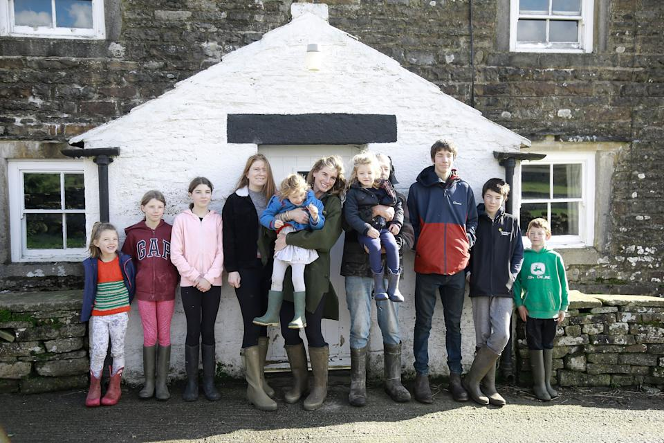 Contributors Amanda and Clive Owen with their children Annas, Violet, Edith, Raven, Clemmy, Nancy, Reuben, Miles, and Sidney outside on Ravenseat Farm.