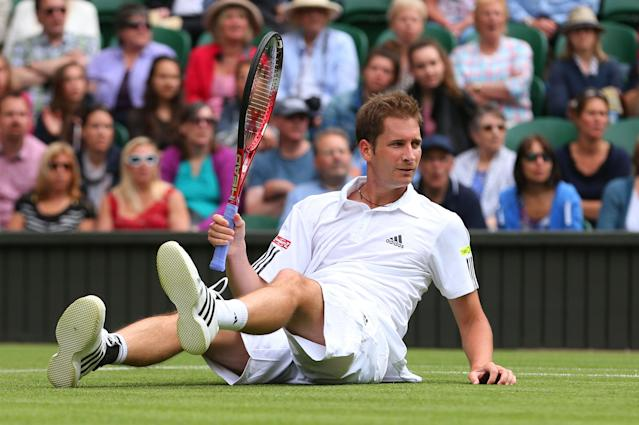 LONDON, ENGLAND - JUNE 25: Florian Mayer of Germany slips during his Gentlemen's Singles first round match against Novak Djokovic of Serbia on day two of the Wimbledon Lawn Tennis Championships at the All England Lawn Tennis and Croquet Club on June 25, 2013 in London, England. (Photo by Julian Finney/Getty Images)