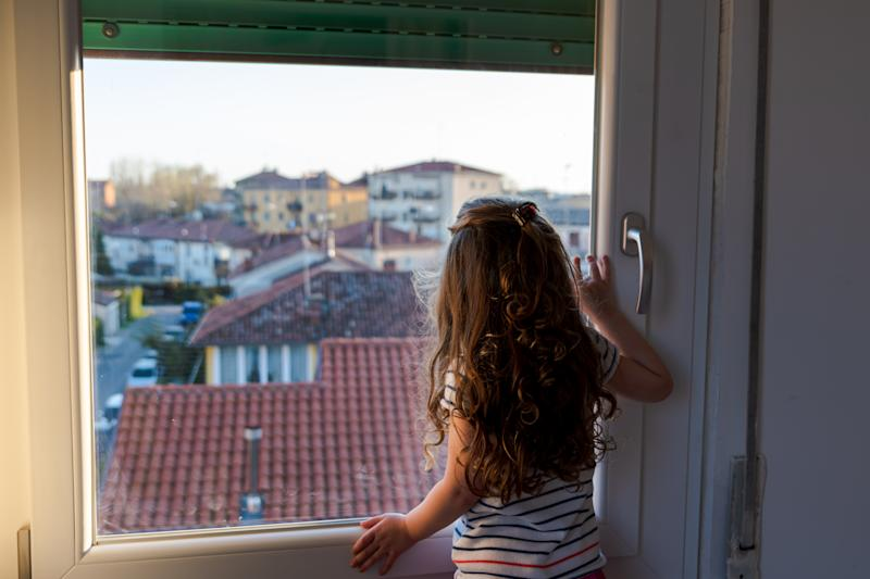 cute little girl spending time looking through the window after a week of quarantine for the cov 19 in italy