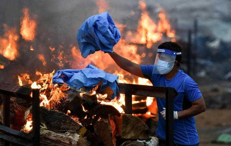 A family member of a Covid-19 victim disposes off his used PPE into the pyre after performing rituals at the quarry in India.