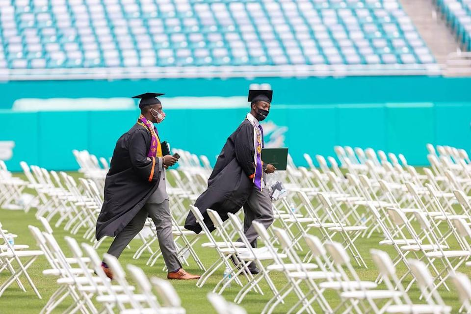 Two students walk across the field at the Hard Rock Stadium in Miami Gardens where the University of Miami spring commencement ceremonies took place on Friday, May 14, 2021.