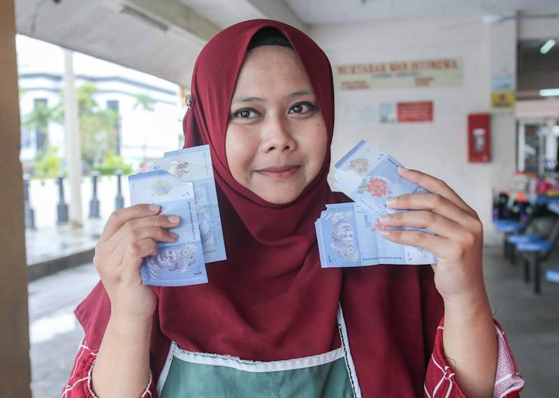 Trader Noor Syazlidn Mohd Yusof shows the torn notes she received from customers.