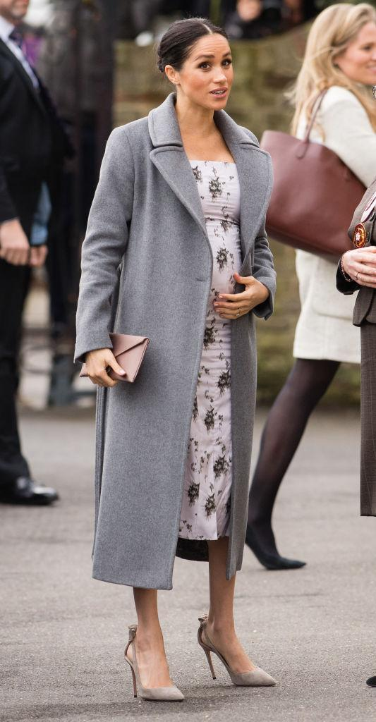 <p>For a trip to Brinsworth House, Meghan chose a £435 Soia and Kyo coat teamed with a £834 floral print panelled midi dress by Brock Collection. She finished the ensemble with her go-to £510 Aquazzura 'Deneuve' suede pumps in powder pink and a £205 Wilbur & Gussie silk oyster clutch bag. She also wore her £1,350 Maison Birks Pétale yellow gold and diamond stud earrings. <em>[Photo: Getty]</em> </p>