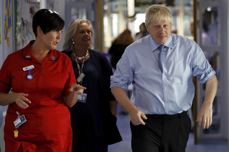 Britain's Prime Minister Boris Johnson is guided during a visit to the Royal Cornwall Hospital in Truro, south-west England, Monday Aug. 19, 2019.   Johnson is under increasing pressure Monday to recall Parliament after leaked government documents warned of widespread problems if the U.K. leaves the European Union without a Brexit withdrawal agreement. (Peter Nicholls/Pool via AP)