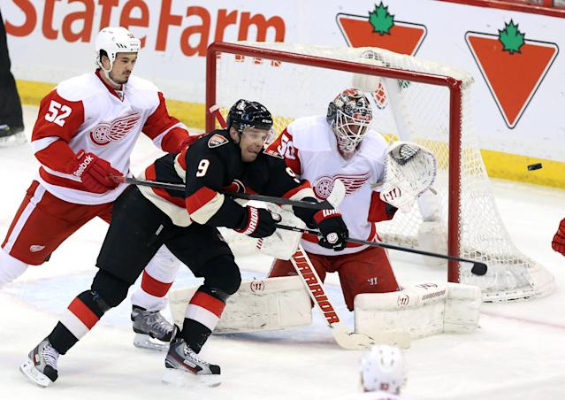 Ottawa Senators' Milan Michalek (9) reaches for a flying puck as Detroit Red Wings goaltender Jonas Gustavsson (50) and Jonathan Ericsson (52) defend during second period NHL hockey action in Ottawa, Thursday, Feb. 27, 2014. (AP Photo/The Canadian Press, Fred Chartrand)