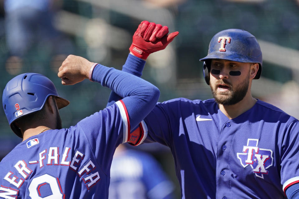 Texas Rangers' Joey Gallo, right, celebrates with Isiah Kiner-Falefa after hitting a two-run home run during the first inning of a spring training baseball game against the Kansas City Royals, Sunday, Feb. 28, 2021, in Surprise, Ariz. (AP Photo/Charlie Riedel)