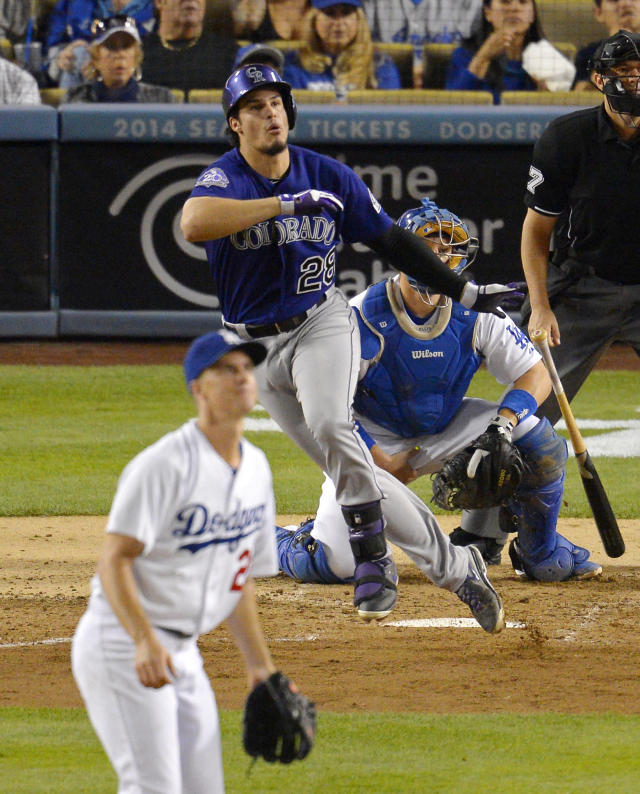 Colorado Rockies' Nolan Arenado, center, hits an RBI double as Los Angeles Dodgers starting pitcher Zack Greinke, left, and catcher A.J. Ellis look on during the fourth inning of their baseball game, Saturday, Sept. 28, 2013, in Los Angeles. (AP Photo/Mark J. Terrill)