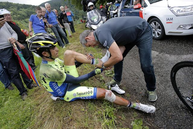 A team member helps Spain's Alberto Contador change race shoes after he crashed during the tenth stage of the Tour de France cycling race over 161.5 kilometers (100.4 miles) with start in Mulhouse and finish in La Planche des Belles Filles, France, Monday, July 14, 2014. Contador withdrew from the race as a result of the crash. (AP Photo/Christophe Ena)