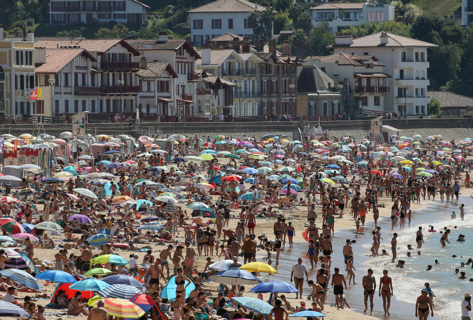 FILE - In this Saturday, July 18, 2020 file photo, people sunbathe in Saint Jean de Luz' beach, southwestern France. France on Friday Oct. 23, 2020 surpassed 1 million confirmed coronavirus cases, becoming the second country in Western Europe after Spain to reach the mark. (AP Photo/Bob Edme, File)