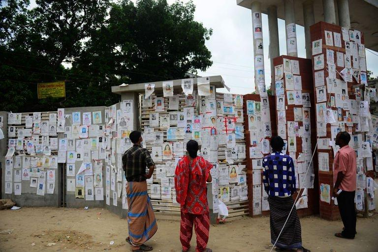 Bangladeshi relatives look at a board posting notices of missing and dead workers  in Savar, on May 4, 2013