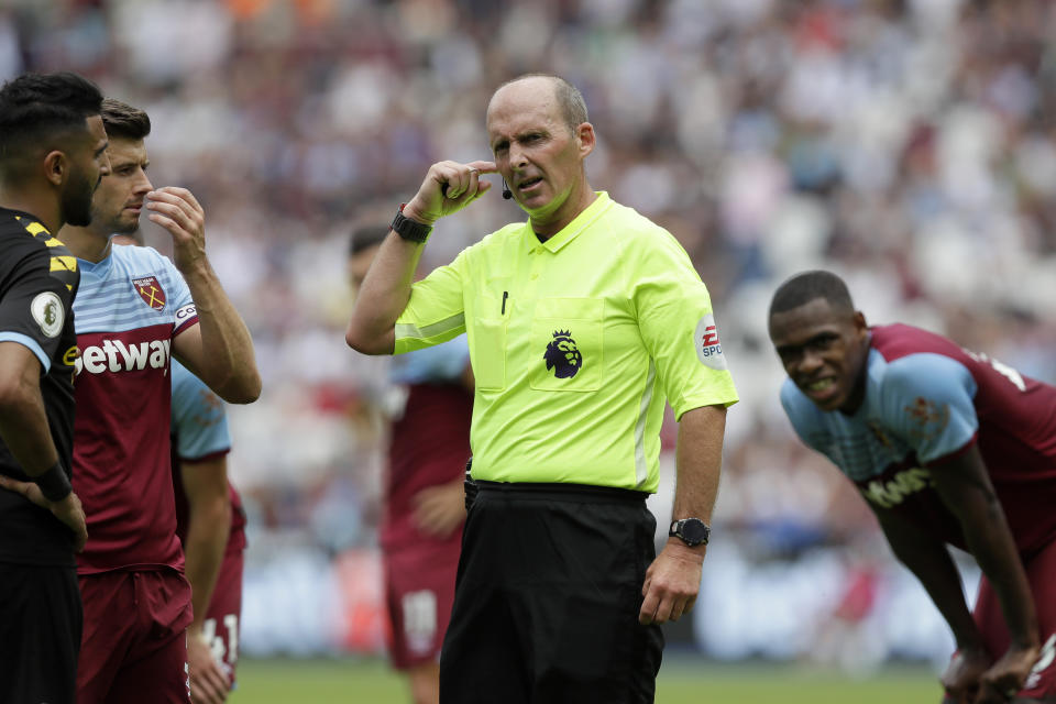 Referee Mike Dean waits for a VAR decision on a penalty during the English Premier League soccer match between West Ham United and Manchester City at London stadium in London, Saturday, Aug. 10, 2019. (AP Photo/Kirsty Wigglesworth)