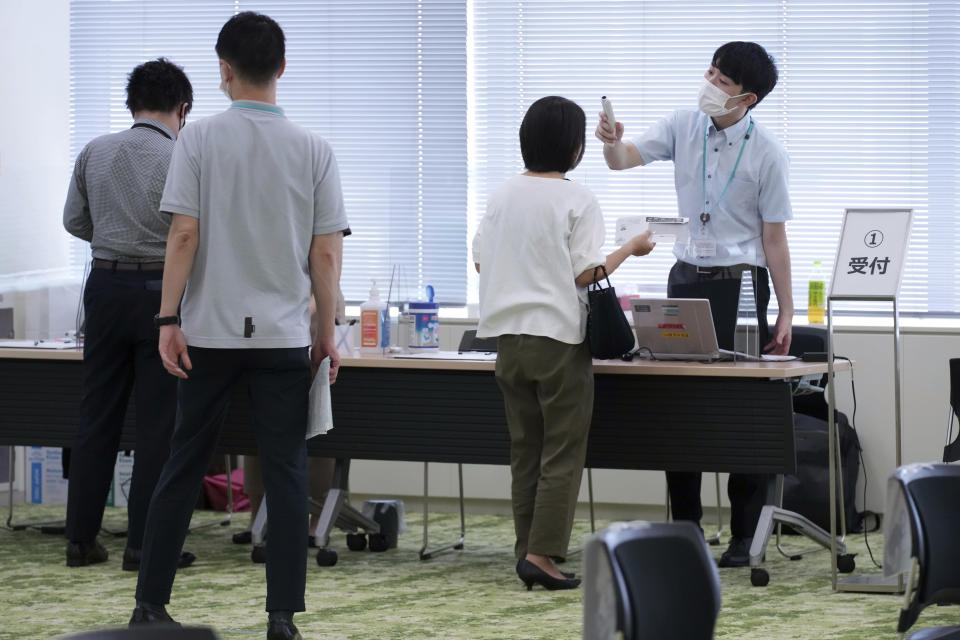 Employees of the beverage maker Suntory register to receive shots of the Moderna COVID-19 vaccine at their office building as the company began its workplace vaccination Monday, June 21, 2021, in Tokyo. Thousands of Japanese companies began distributing COVID-19 vaccines to workers and their families Monday in an employer-led drive reaching more than 13 million people that aims to rev up the nation's slow vaccine rollout. (AP Photo/Eugene Hoshiko)