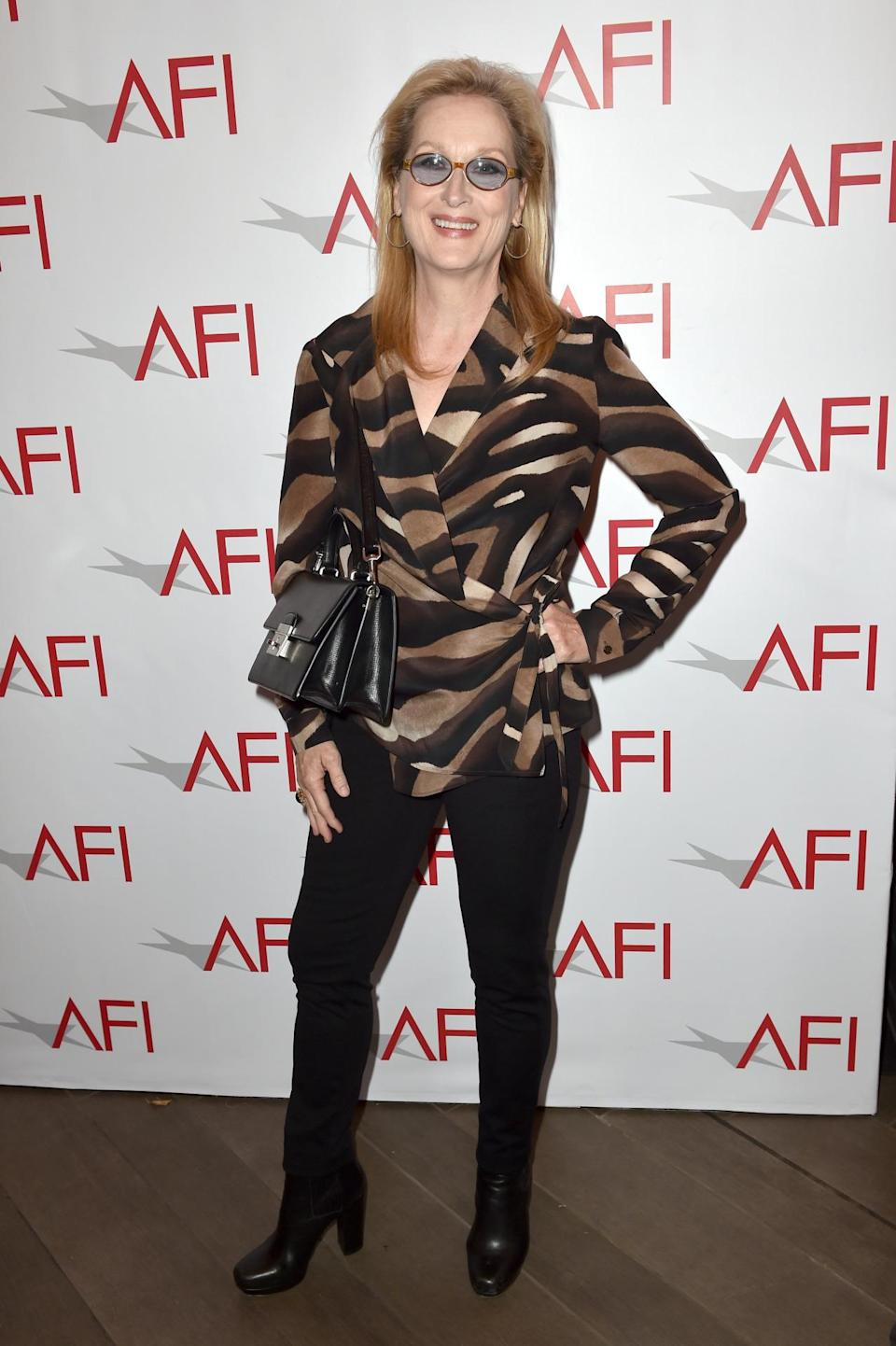 Meryl Streep wore a wrap-around top in animal print with booties and black pants.