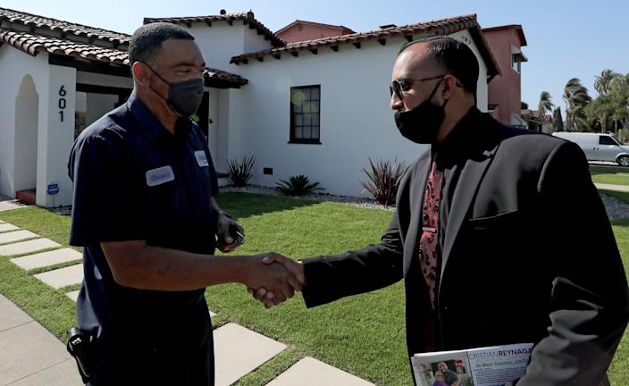 Two men wearing masks shake hands outside a house