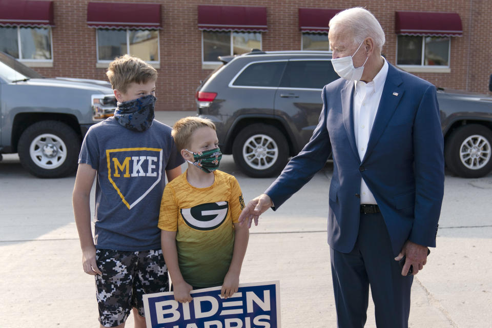 Democratic presidential candidate former Vice President Joe Biden greets children outside of the Wisconsin Aluminum Foundry in Manitowoc, Wis., Monday, Sept. 21, 2020. (AP Photo/Carolyn Kaster)