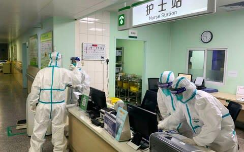 <span>Medical staff members wearing protective suits at the Zhongnan hospital in Wuhan in China's central Hubei province</span> <span>Credit: AFP </span>